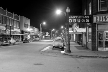 Image of Downtown Sumner in the 1950s looking east on Main Street from Cherry Avenue. Shot at night, image includes cars on the road as well as multiple businesses along Main Street.
