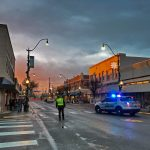 Patrol car with lights on and officer on Main Street with sunset in the background