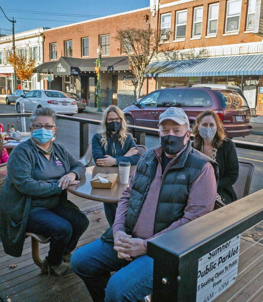 Suzanne Kipfer, Joleen Jones, Mayor Bill Pugh and Jill Starks sitting on Main Street in a parklet with masks on.