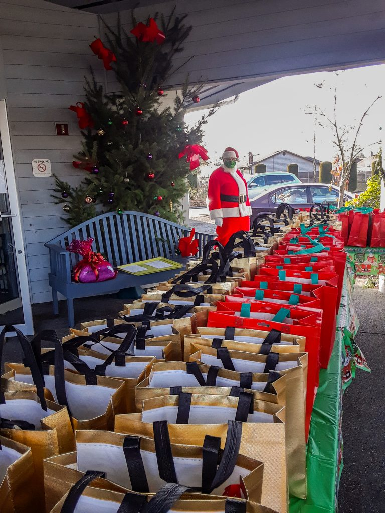 Rows of gift bags with Santa behind them